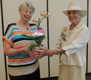 Outgoing Director Anne Simpson, left, presents out going Co-president Carole Biggs with an orchid.